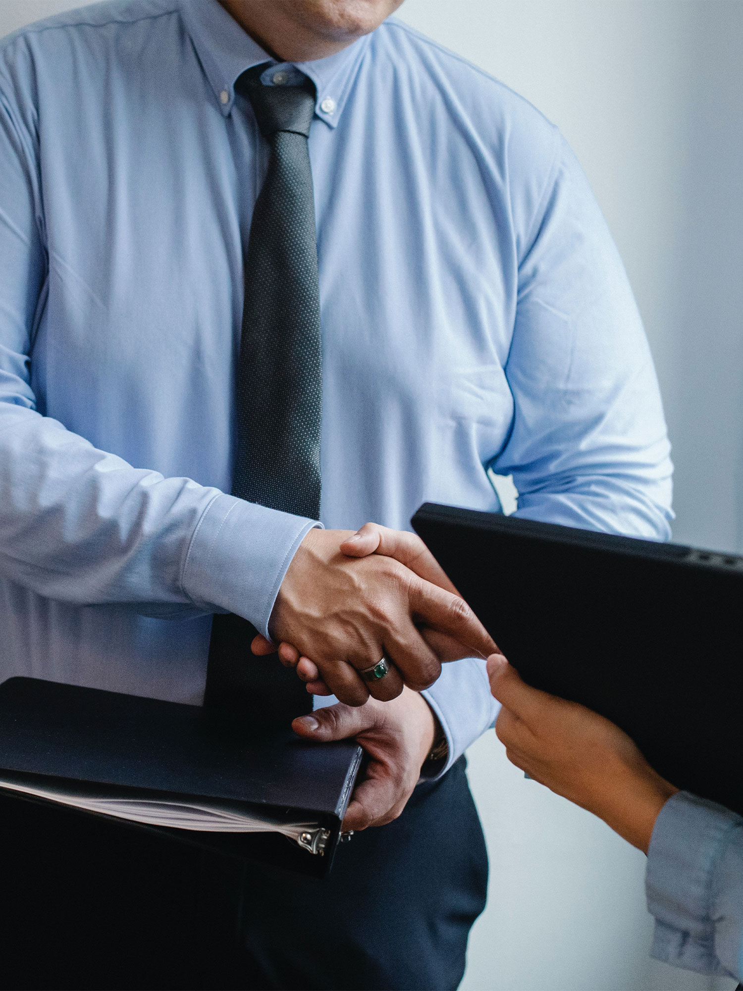 CLose up of a financial advisor shaking hands with a client, who is working towards her long term financial goals