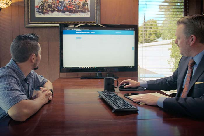 Two men sit at a desk in front of a computer at Blakeslee & Blakeslee, discussing financial planning services